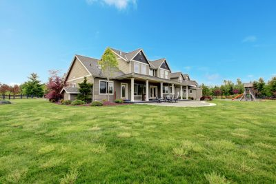 Large farm country house with spring green landscape, kids play ground.